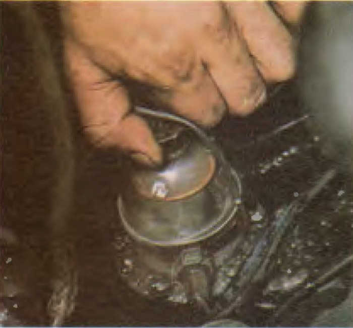Mechanical fuel pumps have a domed top held on by a knurled nut. To service the filter start by removing the nut and dome